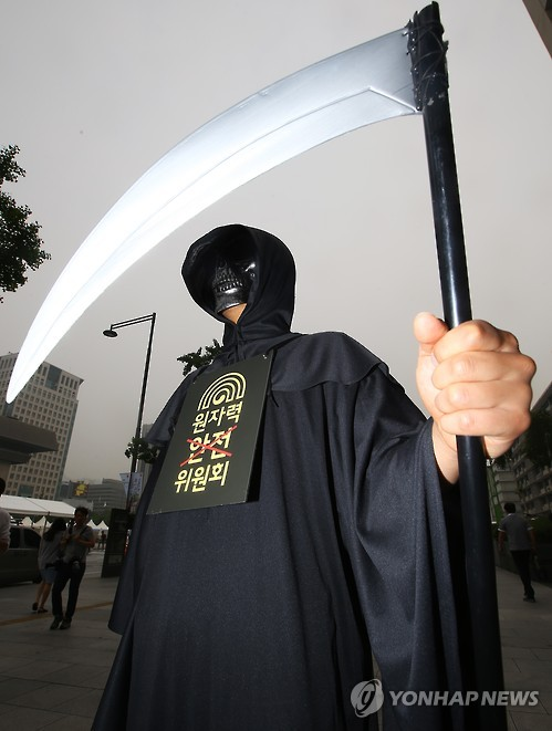 A member of Greenpeace disguised as the Grim Reaper takes part in a rally in Seoul.
