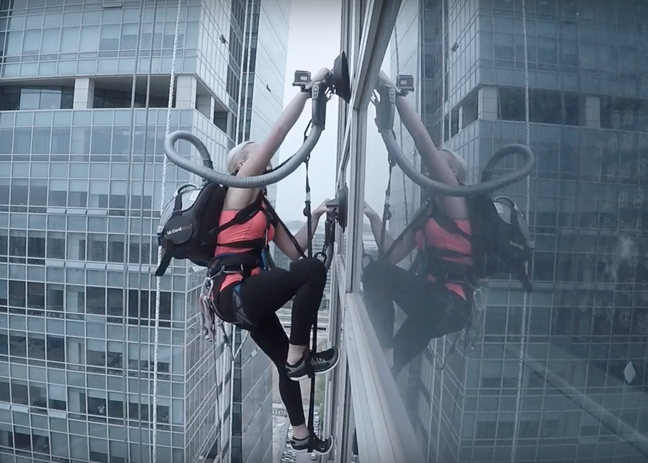 Sierra strapped on two vacuum cleaners, one on each shoulder, and started climbing up the building relying only on suction plates she was holding in each hand. (image: YouTube)