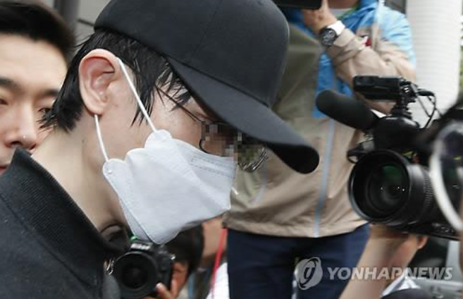Surrounded by reporters, the suspect behind the brutal murder of a 23-year-old woman leaves the Seocho Police Station on May 26. (image: Yonhap)