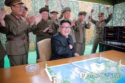 North Korea's top leader Kim Jong-un (seated) and other officials are elated after watching what the country claimed as a successful launch of its Hwasong-10 ballistic missile in this photo released by the Rodong Sinmun, the North's ruling party newspaper, on June 23, 2016. (For Use Only in the Republic of Korea. No Redistribution) (Yonhap)