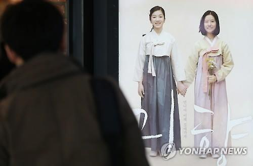 "A moviegoer looks at a poster of the South Korean film ""Spirits' Homecoming"" in Seoul on March 8, 2016. (Image courtesy of Yonhap)"