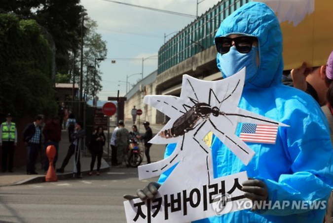 The photo shows an activst protesting against reports of the U.S. military's alleged plan to conduct Zika virus detection tests at its Seoul base. (image: Yonhap)