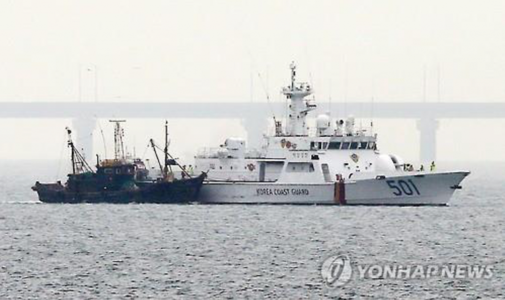 A Chinese fishing boat escorted by a South Korean Coast Guard vessel enters Incheon port, east of Seoul, on June 15, 2016, after being seized by the military policy team for illegal fishing in the neutral waters of the Han River's estuary. (image: Yonhap)