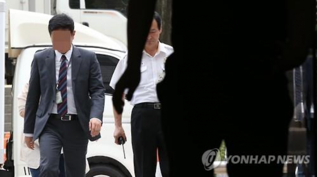 An executive at the local unit of Volkswagen (L), identified only by his surname Yoon, enters the Seoul Central District Court on June 23, 2016. The court issued a warrant to take him into custody on the next day over his alleged involvement in the German carmaker's irregularities that came into light following its emissions scandal. (image: Yonhap)