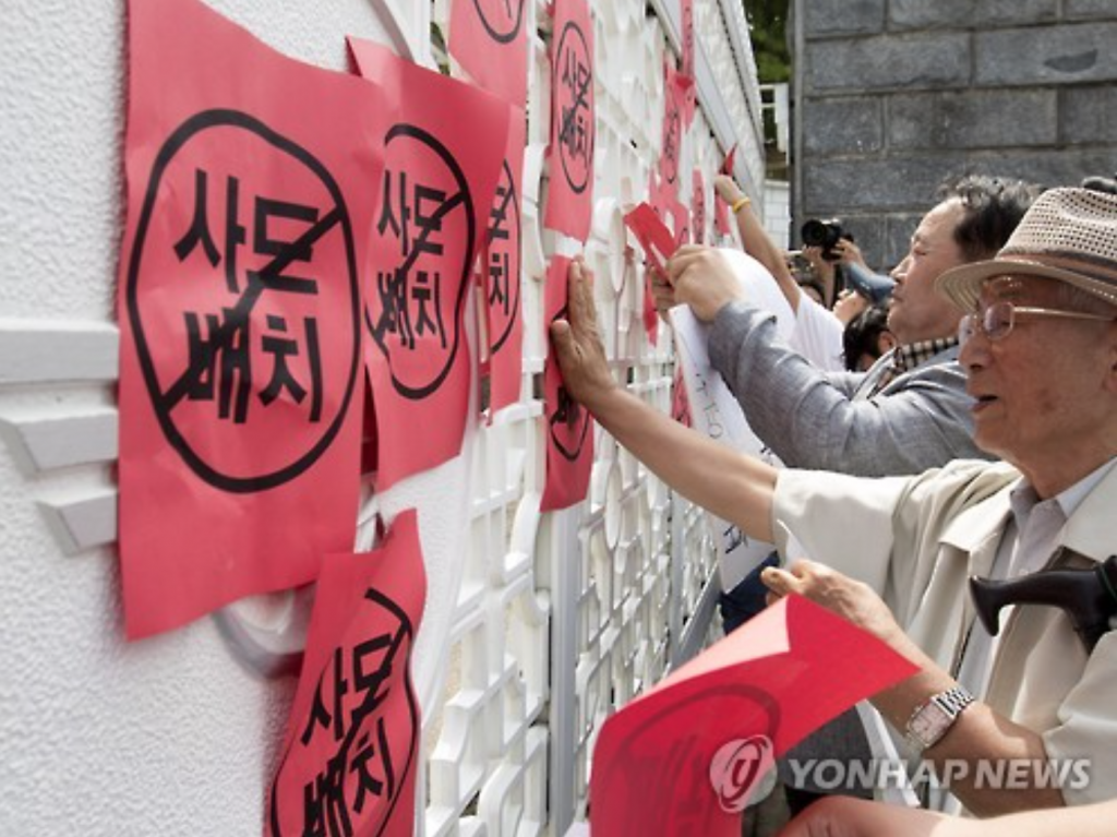 Opposing the deployment of a THAAD system in South Korea, members of a local civic group fix red pieces of paper to the gate of the defense ministry building on July 13.