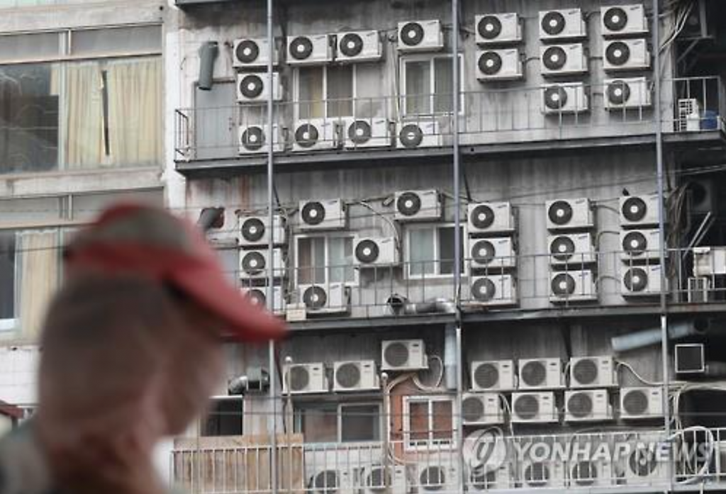 A pedestrian looks at the outdoor units of air conditioners installed on a Seoul building on July 25, 2016, as the nation's electricity demand hit a summer-time high. (image: Yonhap)