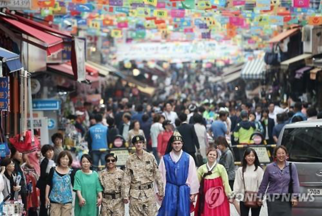 Foreigners -- some wearing traditional Korean clothing, others military uniforms -- take part in the 2016 Namdaemun Market Global Festival on May 26. (image: Yonhap)