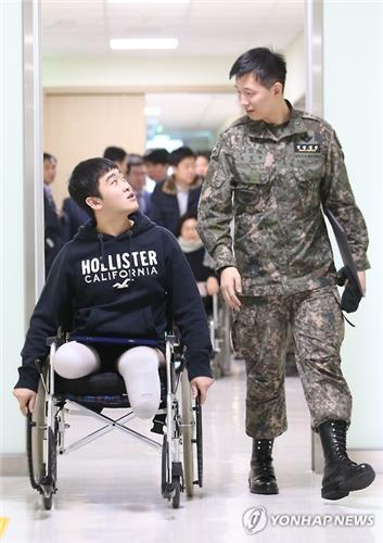 This picture taken on Dec. 14, 2015, shows two soldiers seriously maimed by the North's land-mine attacks near the DMZ in August last year. Ha Jae-heon (L) lost both of his legs and Kim Jeong-won walking beside him lost one leg and wears a prostetic on his right. (image: Yonhap)