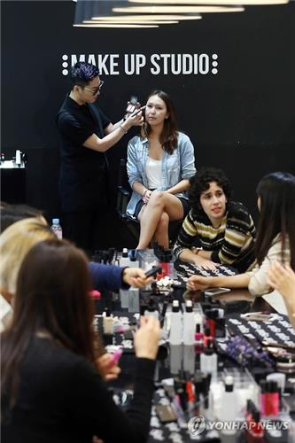 A hallyu makeup experience event for foreign tourists is under way at a store in Seoul on June 15, 2016. (image: Yonhap)