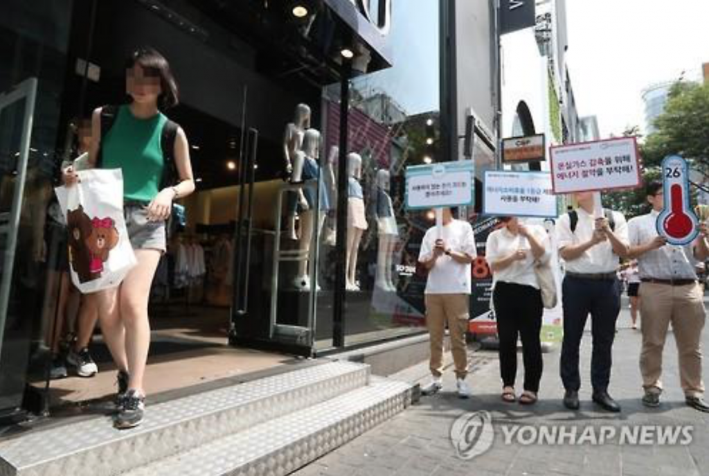 A group of public and private sector officials hold a campaign in Seoul's Myeongdong district on Aug. 8, 2016, to discourage street-side stores from leaving their doors open with air conditioners on. (image: Yonhap)
