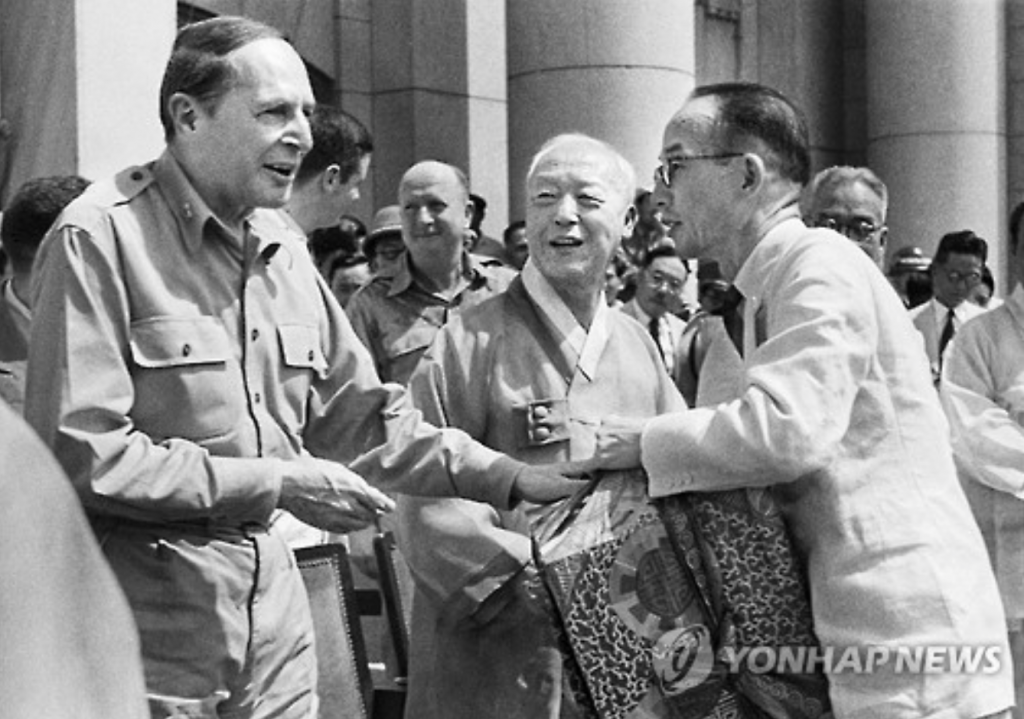 Korea's first president Syngman Rhee (C) with General Douglas MacArthur (L) celebrating the establishment of the South Korean government.