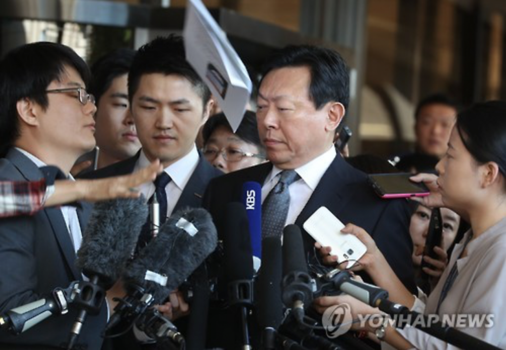 A bunch of papers is hurled by a protester at Shin Dong-bin (C), chief of the embattled South Korean retail giant Lotte Group, as he arrives at the Seoul Central District Prosecutors' Office on Sept. 20, 2016, to face questioning over the group's alleged slush funds and embezzlement. (image: Yonhap)