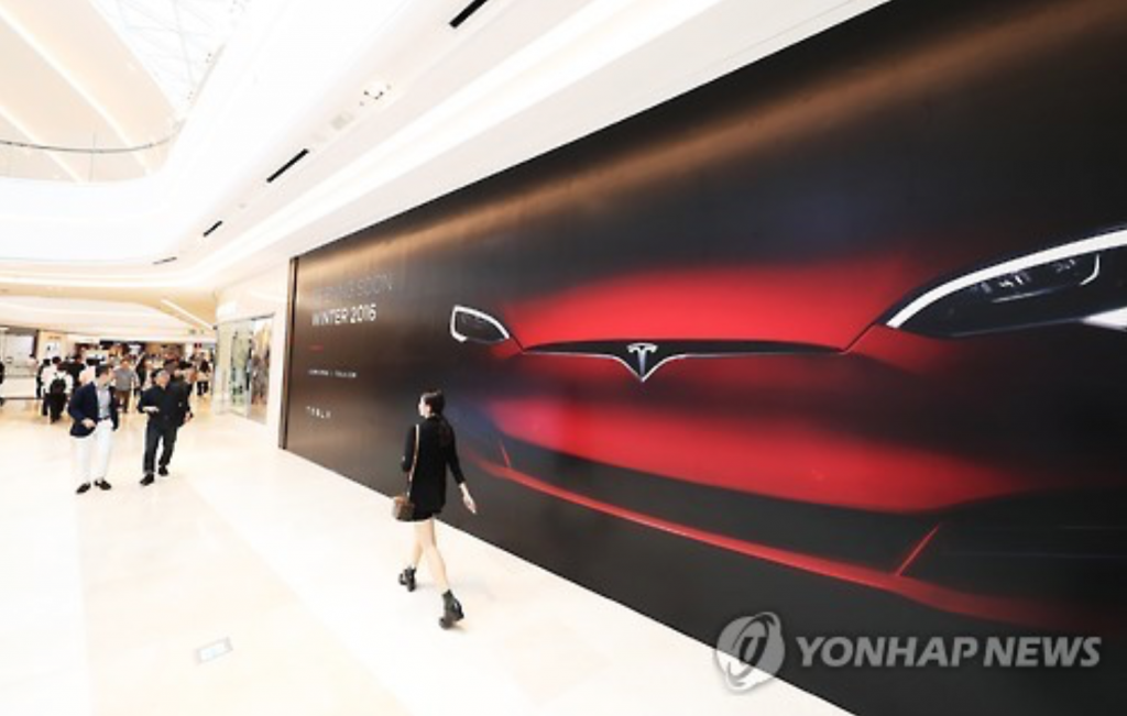 Visitors to Starfield Hanam, a shopping mall east of Seoul, walk past an ad by Tesla on Sept. 5, 2016. The U.S. electric vehicle maker will open its first showroom in Korea at the mall. (image: Yonhap)