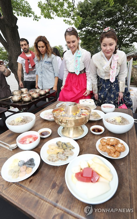 Foreigners in Korean traditional dress, hanbok, look at the royal cuisine during a food festival held in Seoul on Sept. 30, 2016. (image: Yonhap)
