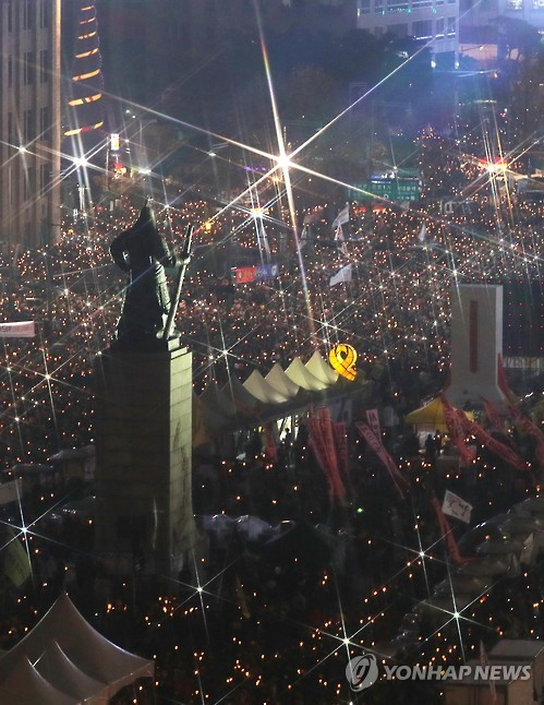 Protesters holding up candles march around Gwanghwamun Square in central Seoul on Nov. 19, 2016, calling for President Park Geun-hye's resignation. (image: Yonhap)