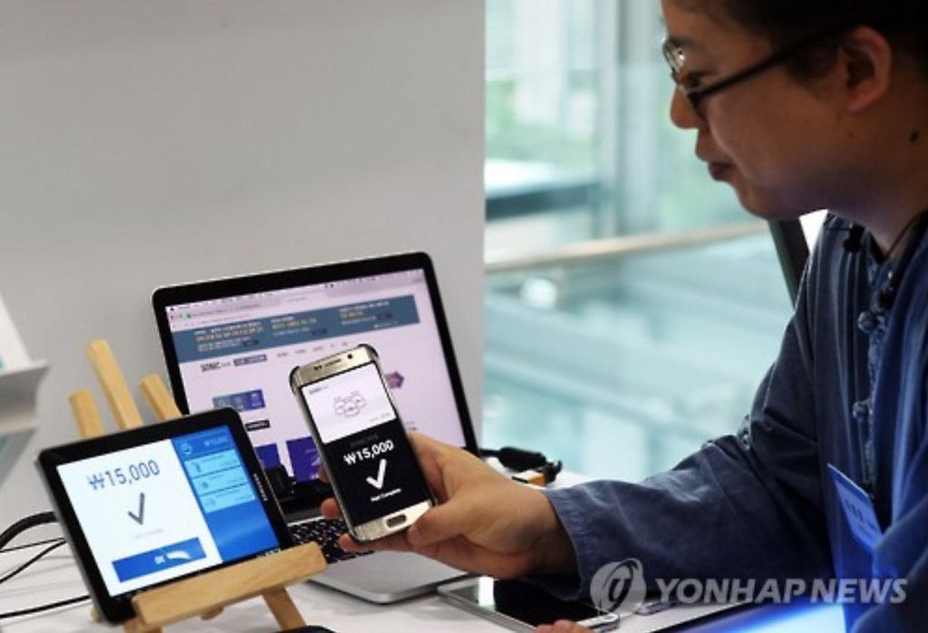 A South Korean fintech firm official shows a mobile wallet service during the 11th Demo Day event in this file photo dated on Sept. 26, 2016. (image: Yonhap)