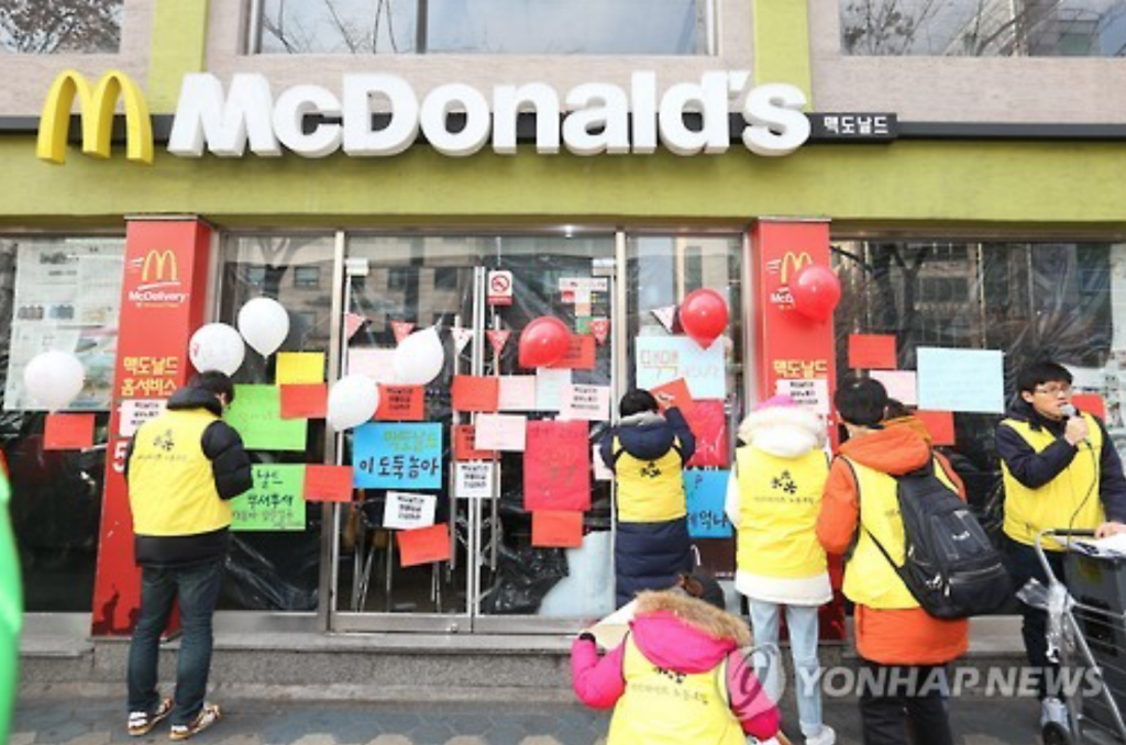 On Tuesday afternoon, former employees and members of the Alba Organization, Korea's labor union for part-time workers, protested in front of the now-closed Mangwon outlet, affixing signs festooned with angry slogans to the front of the building. (image: Yonhap)