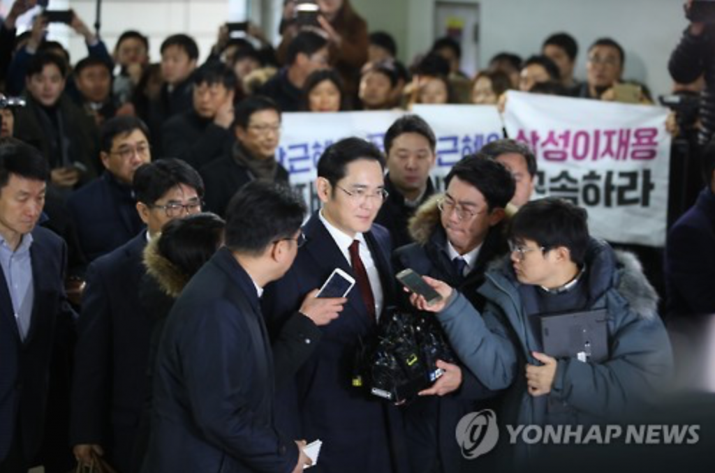 Samsung Electronics Vice Chairman Lee Jae-yong (C) is surrounded by reporters as he arrives at the investigation team's office in southern Seoul on Jan. 12, 2017. (image: Yonhap)
