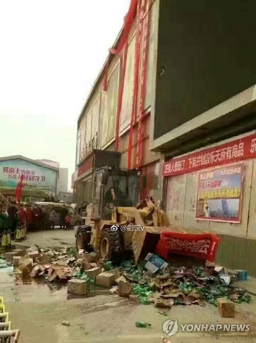 This photo, taken on March 5, 2017, from the Chinese microblog Weibo, shows products of South Korea's Lotte Chilsung Beverage Co. being destroyed by a bulldozer at a wholesale market in China's Henan Province, as China has been expressing strong hostility toward South Korea's decision to allow the deployment of an advanced U.S. missile defense system in the country. (Yonhap)