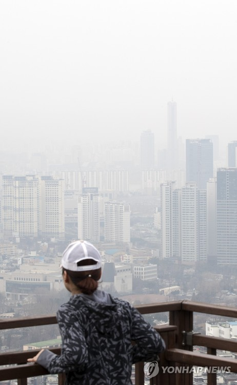A woman gazes out at downtown Seoul from an observation deck on Mount Nam on March 20, 2017, as the city is covered in a dim haze caused by fine dust. (image: Yonhap)