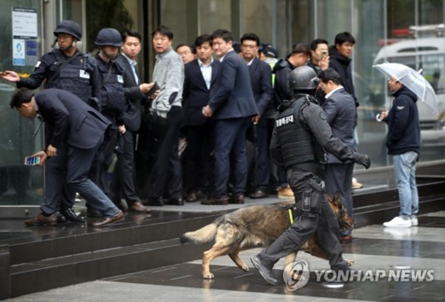 Samsung Life Insurance employees look on while police conduct a search of the company building in southern Seoul on April 14, 2017. (Image: Yonhap)