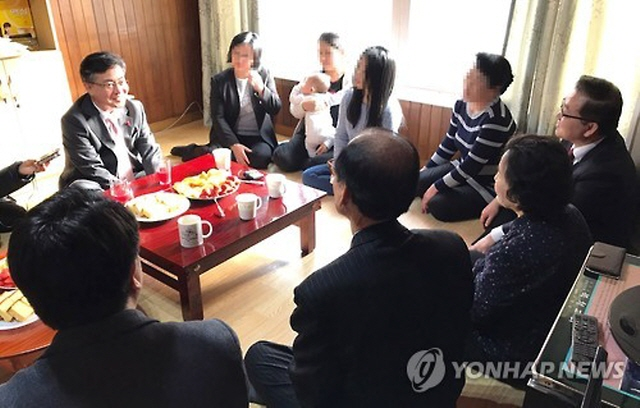 Unification Minister Hong Yong-pyo (L) talks with North Korean defectors at a shelter in an undisclosed location in South Korea. (image: Yonhap)