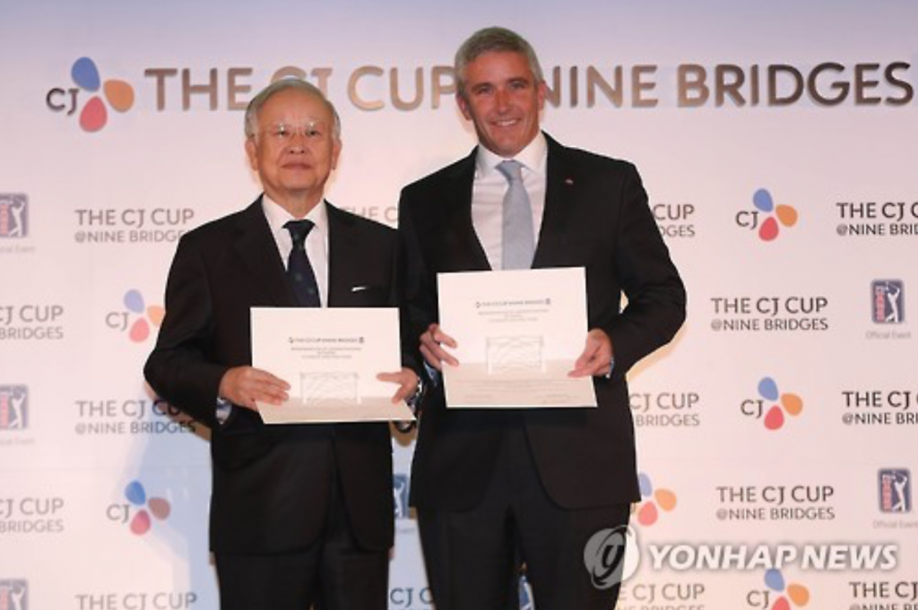 Sohn Kyung-shik, chairman of CJ Group (L), and Jay Monahan, then deputy commissioner of the PGA Tour, pose with their agreements in Seoul after CJ signed on to host the CJ Cup@Nine Bridges, the first PGA Tour event in South Korea. (image: Yonhap)