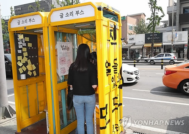 "Since construction began in March, light blue-colored telephone booths have been painted yellow and covered with the message ""We all have a right to read"" in a Korean Ming-style font, giving the booths a fresh new look. (Image: Yonhap)"