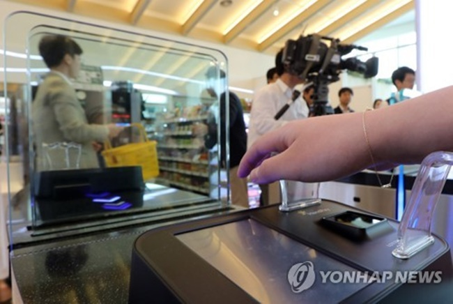 The vein-scanning self-checkout terminal studies the size, color, and shape of each shopper's veins, which are then translated into numeric figures allowing shoppers to make payments without the hassle of using a cell phone, credit card or cash, after registering their Lotte Card user information. (Image: Yonhap)