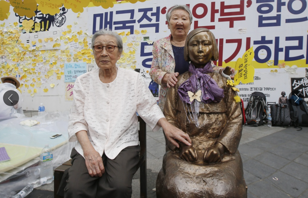 Former confort women Kim Bok-dong (L) and Gil Won-ok poses for a photo next to comfort woman statue in front of the Japanese Embassy in Seoul on August 14, 2016, the International Memorial Day for Comfort Women. (image: Yonhap)