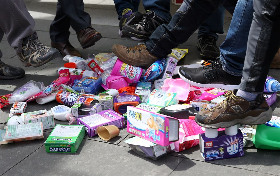 Victims and members of environmental organizations trample Oxy products as part of their protest on April 28, 2016, in front of the International Finance Center Seoul. (image: Yonhap)