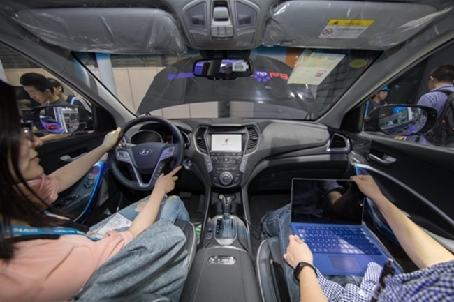 In this photo taken on June 7, 2017, and provided by Hyundai Motor Co., Chinese consumers test the navigation and voice recognition systems in a Santa Fe Tucson SUV displayed at the CES ASIA 2017 in Shanghai. (Image: Yonhap)
