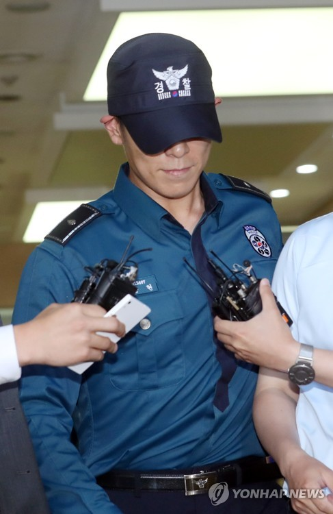South Korean singer and actor T.O.P. of boy band BIGBANG, who is serving his mandatory military service as a conscripted policeman, leaves his workplace in Seoul surrounded by reporters questioning his marijuana charges on June, 5, 2017. (image: Yonhap)