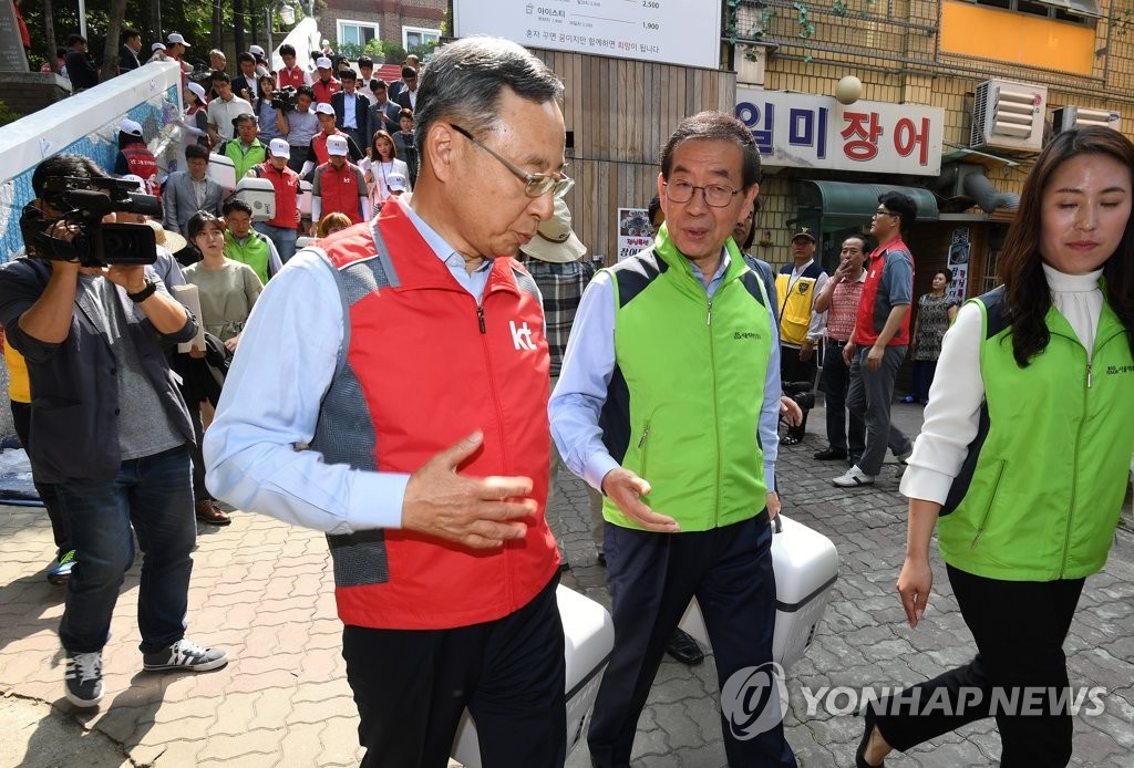 Along with the plans for smart sensors, Seoul Mayor Park Won-soon and KT CEO Hwang Chang—gyu met at an event held on Wednesday celebrating the third anniversary of a local welfare center for residents living in poor housing conditions, after which the two donated small refrigerators to those in need. (Image: Yonhap)