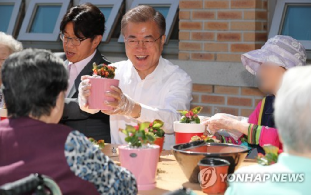 President Moon Jae-in holds up a pot of flowers that he made with senior citizens at a state-operated nursing home in Seoul on June 2, 2017. (image: Yonhap)