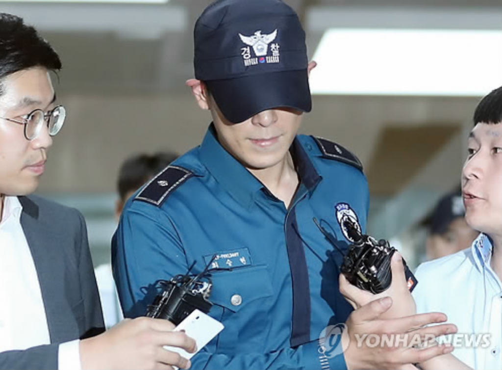 T.O.P, who's been serving his mandatory military service as a conscripted policeman, leaves his workplace in Seoul surrounded by reporters questioning his marijuana charges on June, 5. (image: Yonhap)