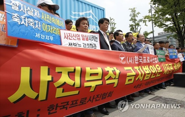 Members of an association of private photo studio owners held a rally Thursday in front of the office of President Moon Jae-in's power transition team in downtown Seoul, insisting that the ongoing push for the resume photo ban in the public sector will threaten the livelihoods of about 300,000 photo studios nationwide. (Image: Yonhap)