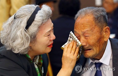 South Korean Lee Jung-sook (L) with a handkerchief wiping away the tears of her father Lee Heung-jong from North Korea at family reunions. (image: Yonhap)