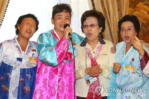 "Separated South and North Korean families singing the song ""Our wish is unification"" together at family reunions. (image: Yonhap)"