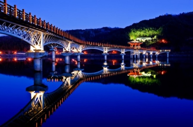 The area surrounding Woryeonggyo, Korea's longest wooden bridge, is famous for its nocturnal charms, thanks to the beauty of the wooden docks and the dams and balancing reservoirs in the background. (Image: Andong City Government)