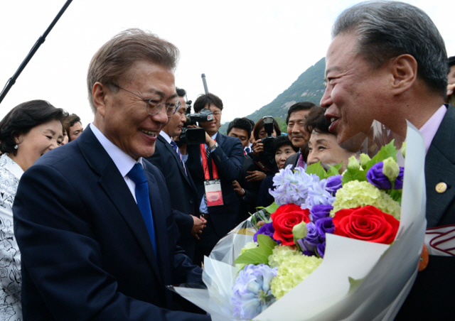 President Moon Jae-in receives welcome flowers from his new neighbors who live near the presidential office Cheong Wa Dae in Seoul