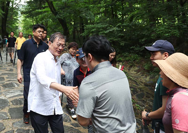 President Moon Jae-in shake hands with a group of visitors at a mountain in Pyeongchang, Gangwon Province, on July 31, 2017, the first day of his five-day summer vacation. (image: Cheong Wa Dae)