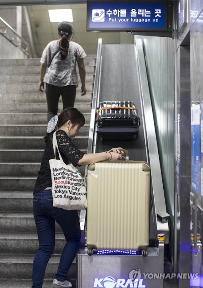 The plight of travelers lugging 20 to 30 kilograms suitcases up and down the stairs of Seoul Station apparently caught the Korea Railroad Corporation's notice, as it announced that conveyor belts had been installed along the stairways leading to and from the subway and the railroad. (Image: Yonhap)