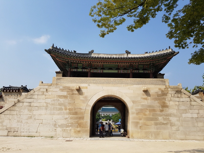 A group of tourists and visitors gathered outside of the northern gate of Gyeongbok Palace to take their pictures in front of South Korea's presidential office Cheong Wa Dae that can be seen through the open, arched gate of Gyeongbok Palace. (image: Yonhap)