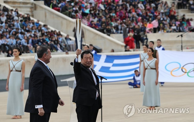 Spyros Capralos, who leads the Hellenic Olympic Committee, passed the flame to Lee Hee-beom, president of the PyeongChang Organizing Committee for the 2018 Olympic & Paralympic Winter Games (POCOG), at the Panathenaic Stadium in Athens. (Image: Yonhap)