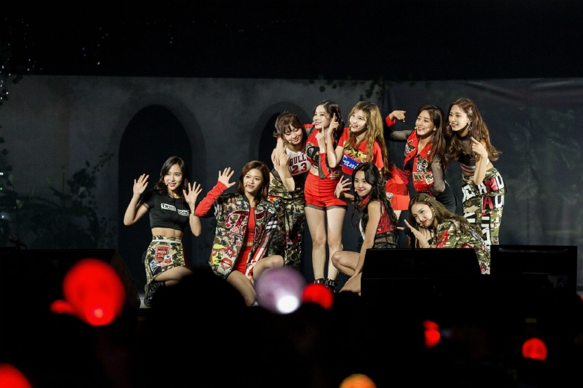 Girl group TWICE waving to fans on stage during a two-day meet-and-greet event marking its two-year debut anniversary at Kyunghee University in Seoul held Oct. 14-15. (image: JYP Entertainment)