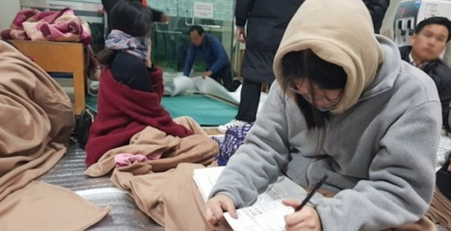 "One 18-year-old said, ""[After the news], my friends burst into tears, and everything was very confusing. I had been mentally prepared, but now that the test is postponed, I don't know what to think. I wish they had found a different solution."" (Image: Yonhap)"