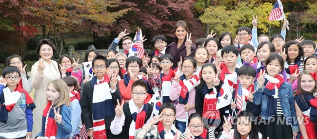 South Korean First lady Kim Jung-sook and U.S. first lady Melania Trump greeted a group of visiting schoolchildren on Tuesday, including family members of U.S. military and diplomatic personnel, after a stroll around the Blue House. (Image: Yonhap)