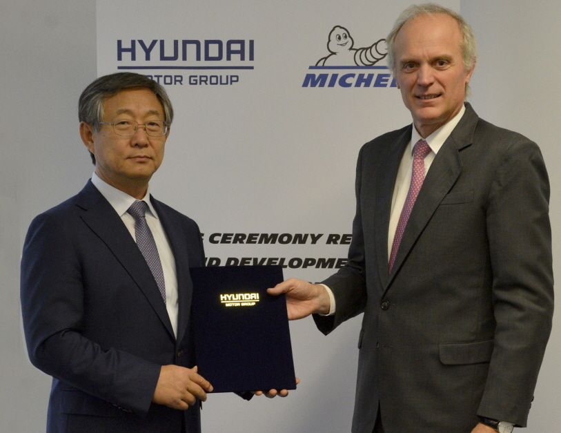 Yang Woong-cheol (L), a Hyundai Motor vice chairman, posing with his Michelin counterpart Florent Menegaux after signing a tie-up agreement at Michelin's Research and Development Center in Clermont-Ferrand in central France. (image: Hyundai motor)