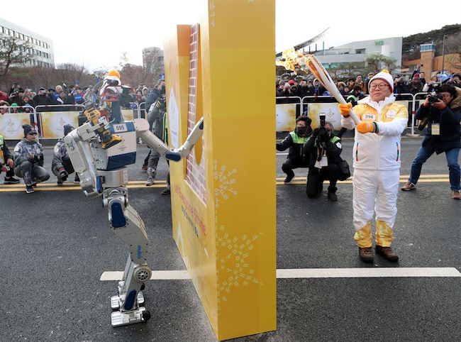 "After Hong passed on the Olympic flame, HUBO pressed forward and successfully transported the fire to the next runner, its ""father"", professor Oh Joon-ho, the leader of Team KAIST. (Image: Yonhap)"